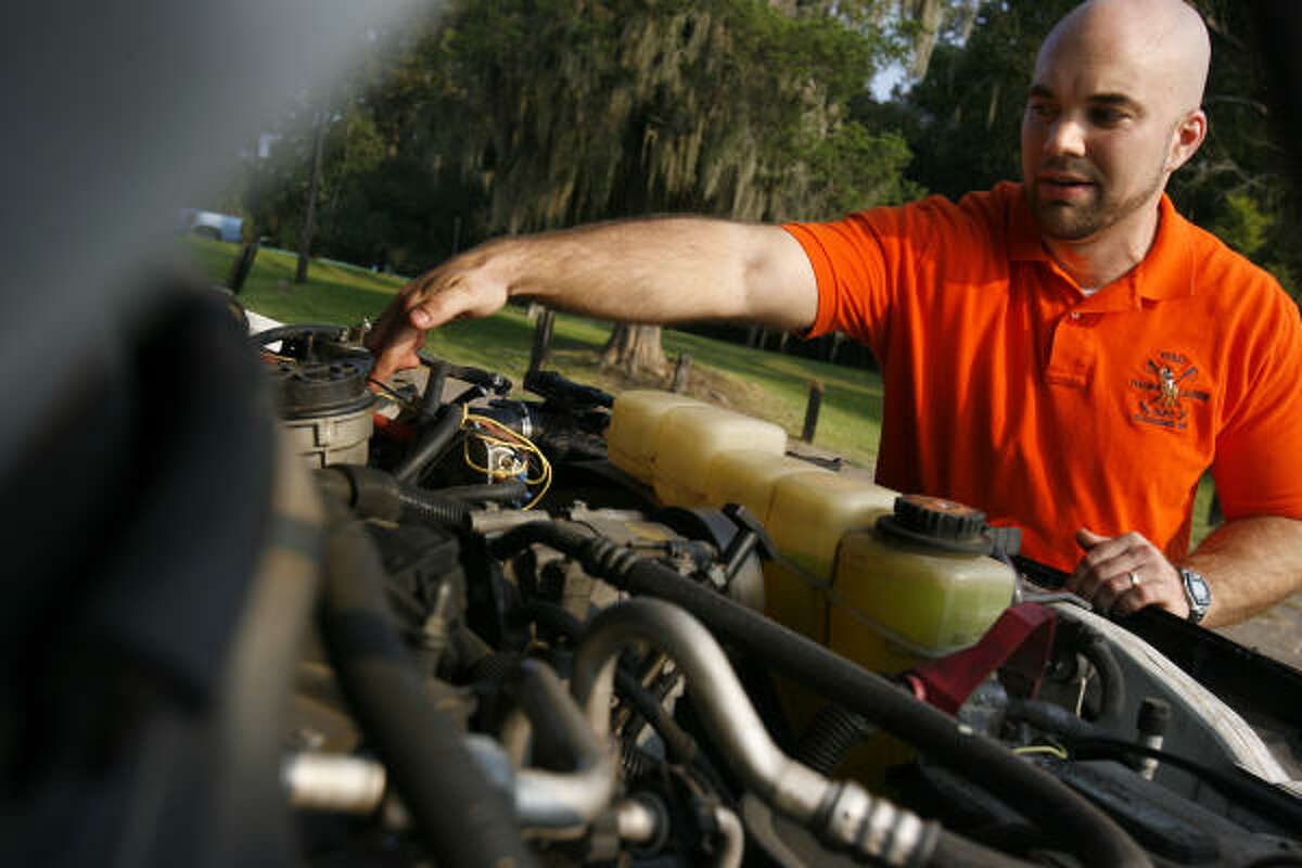 Paul Edwards shows the location of the vegetable oil fuel filter in the engine of his Ford F-250 pickup.