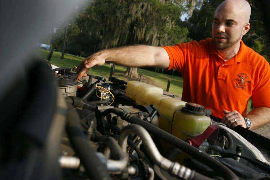 Paul Edwards shows the location of the vegetable oil fuel filter in the engine of his Ford F-250 pickup. Photo: Sharon Steinmann, Houston Chronicle