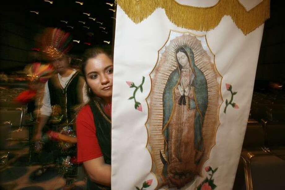 Stephanie Sauzedo, from Corpus Christi Catholic Church in Houston, holds an Our Lady of Guadalupe icon flag before her church's performance at the George R. Brown Convention Center on Sunday. Photo: JOHNNY HANSON, CHRONICLE