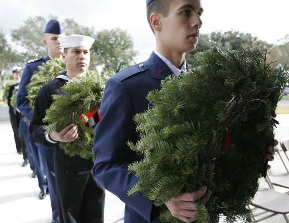 A wreath held by Civil Air Patrol Cadet Jonathan Williams, lined up Saturday at Houston National Cemetery, was one of more than 5,000 placed on headstones across the nation. Photo: KAREN WARREN, CHRONICLE