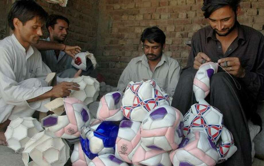 Pakistani laborers stitch soccer balls at a small factory in Sialkot. Thursday's assassination of Benazir Bhutto complicates business relations with the United States. Photo: K M CHAUDARY, ASSOCIATED PRESS FILE