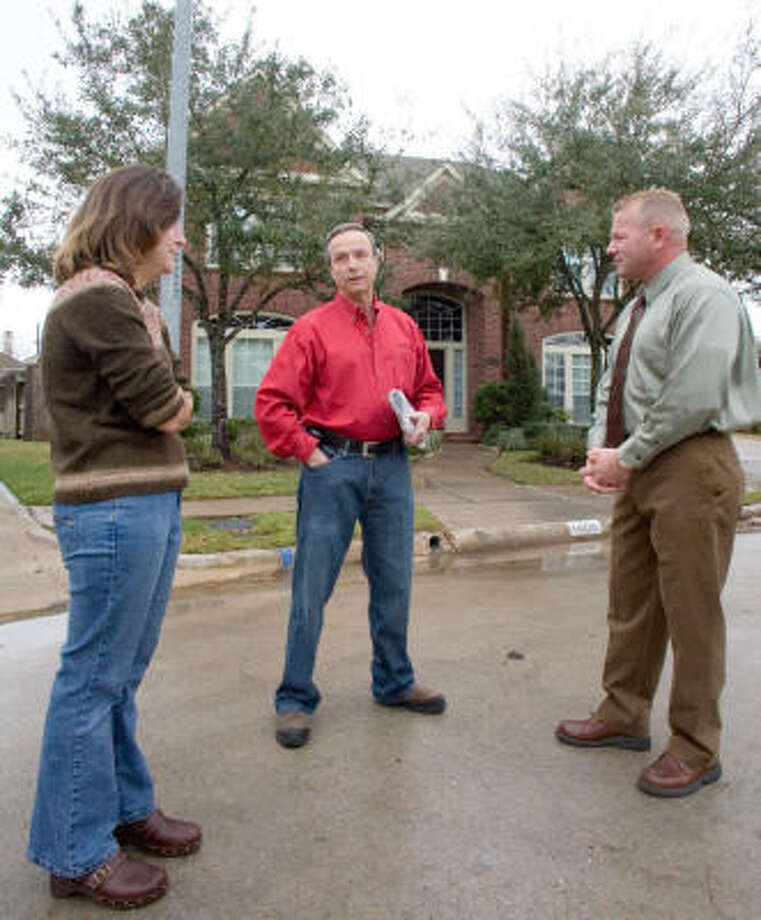 Sugar Land resident Stephanie Reilly, left, independent newspaper distributor Durand Boser  and Fort Bend County Constable Troy Nehls chat outside Reilly's New Territory home. Photo: R. Clayton McKee, For The Chronicle