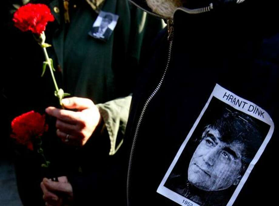 Turkish mourners carry floral tributes to journalist Hrant Dink, whose views on the 1915-18 killings of Armenians likely spurred his assassination outside his newspaper's Istanbul office. Photo: SEZAYI ERKEN, AFP/GETTY IMAGES