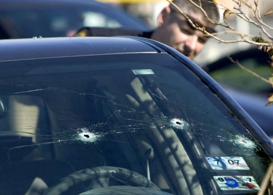 An Humble police officer looks at bullet holes in the windshield of the car of a man who is accused of trying to run over two Houston Police detectives Friday outside a restaurant near Deerbrook Mall. The humble man is expected to survive. Photo: BRETT COOMER, CHRONICLE