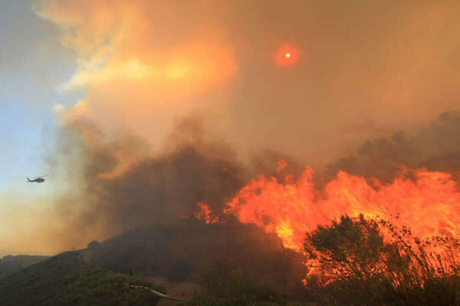 A firefighting helicopter prepares to drop water on the Porter Ranch fire as it threatens homes Monday in the Los Angeles area. Photo: David McNew, Getty Images