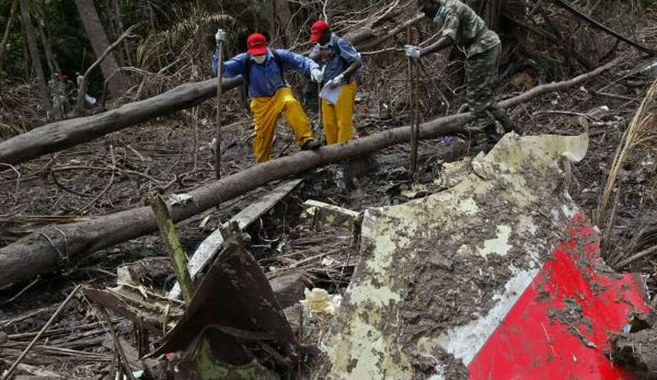 Rescue workers move about the crash site of a Kenya Airways Boeing 737 in Mbanga Pongo, Cameroon, on May 8. The crash, which killed all 114 people aboard, renewed concerns about the safety of African air travel. Photo: SUNDAY ALAMBA, ASSOCIATED PRESS