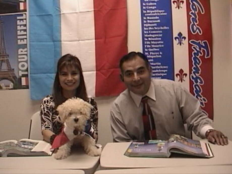 Patricia and Horacio Pedraza Patricia with their 4-month-old French poodle who has been designated as the school mascot at the Texas School of Languages in Cy-Fair. Photo: Stephanie King, For The Chronicle