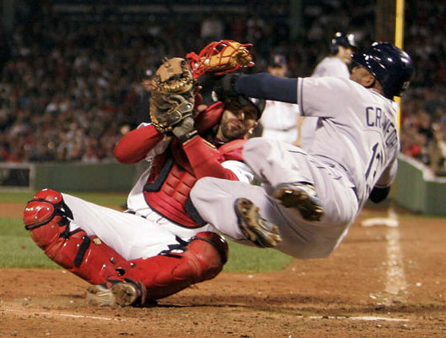 Tampa Bay Rays' Carl Crawford runs into Boston Red Sox catcher Jason Varitek as he tries to score on a single by Dioner Navarro in the eighth inning. Photo: Elise Amendola, AP