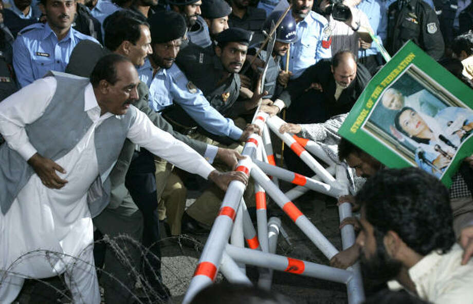Opposition supporters of Pakistan People's Party, PPP, push barricades during a protest against President Gen. Pervez Musharraf in front of the Presidential Office in Islamabad today. Photo: Wally Santana, AP