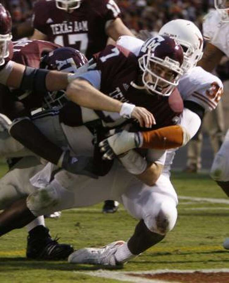 Texas A&M quarterback Stephen McGee takes Texas defensive end Eddie Jones (32) into the end zone for a touchdown in the third quarter. In addition to running for a TD, the junior quarterback was 25-of-36 passing for 362 yards and three touchdowns. Photo: KEVIN FUJII, CHRONICLE