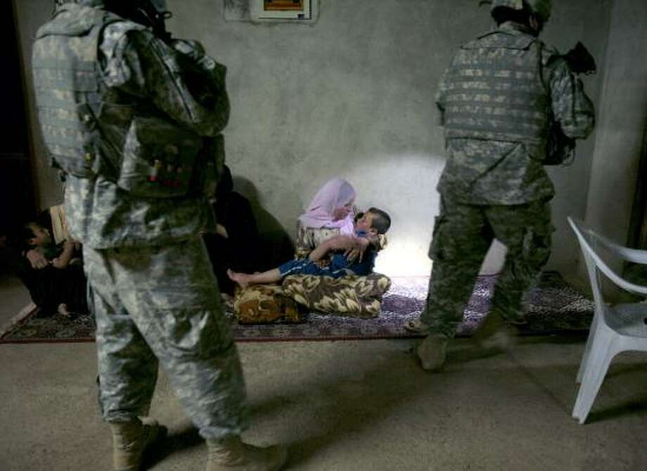 A woman holds her child in Mosul, Iraq, as U.S. soldiers search for a man suspected of being affiliated with al-Qaida in this May 3 photo. Al-Qaida fighters forced out of Baghdad have tried to regroup. Photo: MAYA ALLERUZZO, AP FILE