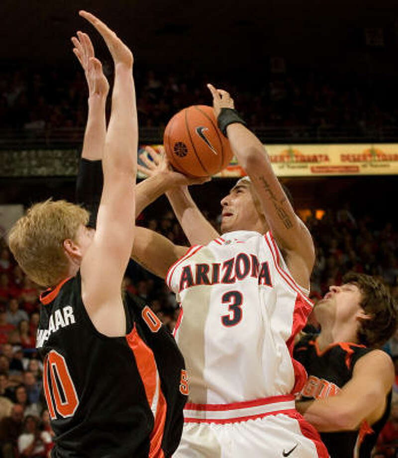 On his way to a career-high 27 points, Arizona's Marcus Williams shoots over Oregon State's Roeland Schaftenaar, left, and Jack McGillis in the Wildcats' 83-72 victory. Photo: Wily Low, AP