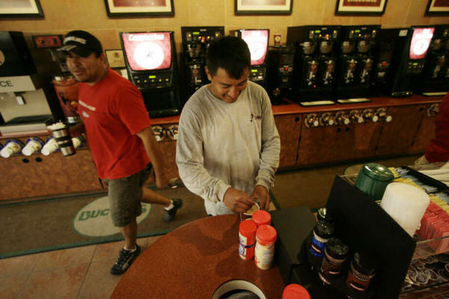 Marco Antonio Perez, center, stirs his coffee at the coffee bar at Buc-ee's in Pearland. Perez, who works in the area, said he buys coffee at the store every morning on his way to work. Photo: Julio Cortez, Chronicle