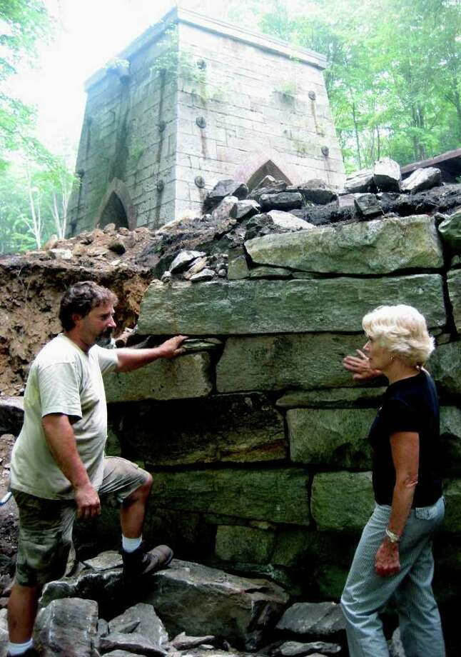 SPECTRUM/The Roxbury Land Trust is working this summer to stabilize stonewalls at the historic, 19th-century iron ore mining complex at its Mine Hill Preserve. Above, Susan Payne, the trust's executive director, discusses the project with Thomas Walker, the contractor doing the restoration work. August, 2011  Courtesy of the Roxbury Land Trust Photo: Contributed Photo