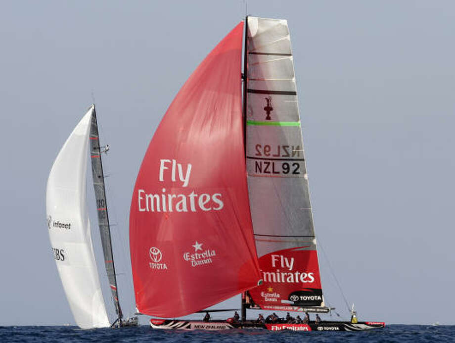 Emirates Team New Zealand, right, sails past Swiss Defender Alinghi during race three of the 32nd America's Cup off the coast of Valencia, Spain. Photo: Fernando Bustamante, AP