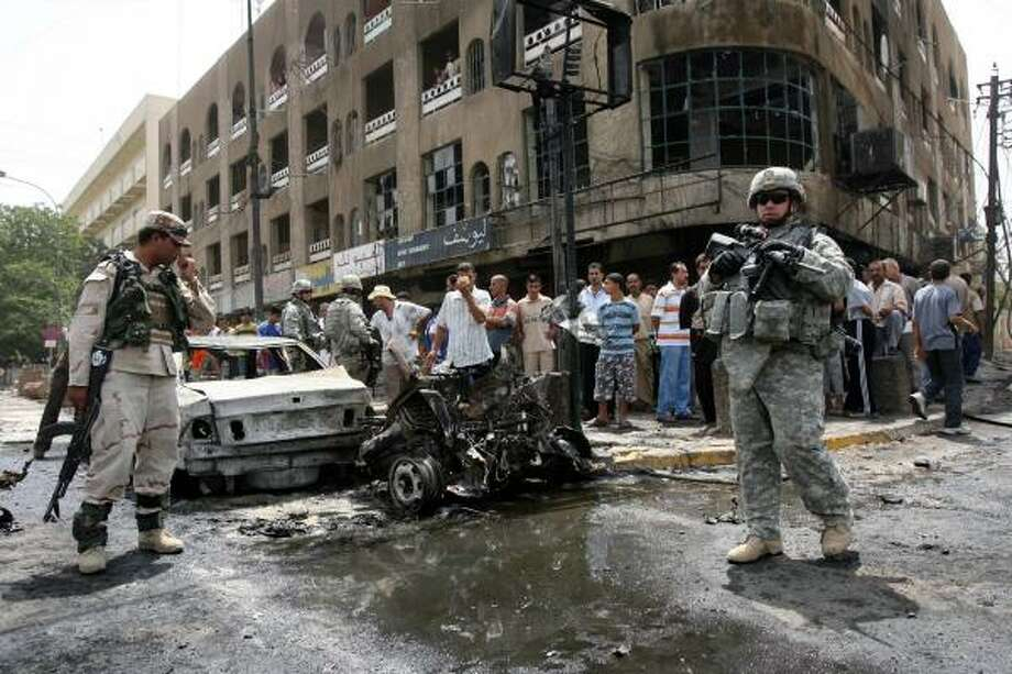 An Iraqi soldier and U.S. soldier stand at the site of a car bomb in the predominantly Shiite Karradah neighborhood Monday. Photo: KHALID MOHAMMED, ASSOCIATED PRESS