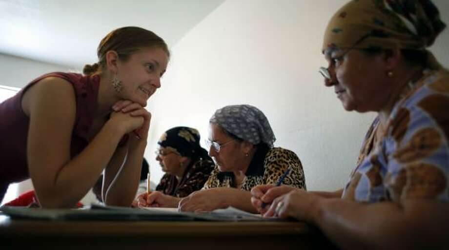 Jessica Martone, left, of Pasadena, Calif., a Jesuit Volunteer Corps member, teaches English to Rashinaz Aydinova, one of several in a group of recent immigrants. Photo: STEVE UECKERT, CHRONICLE