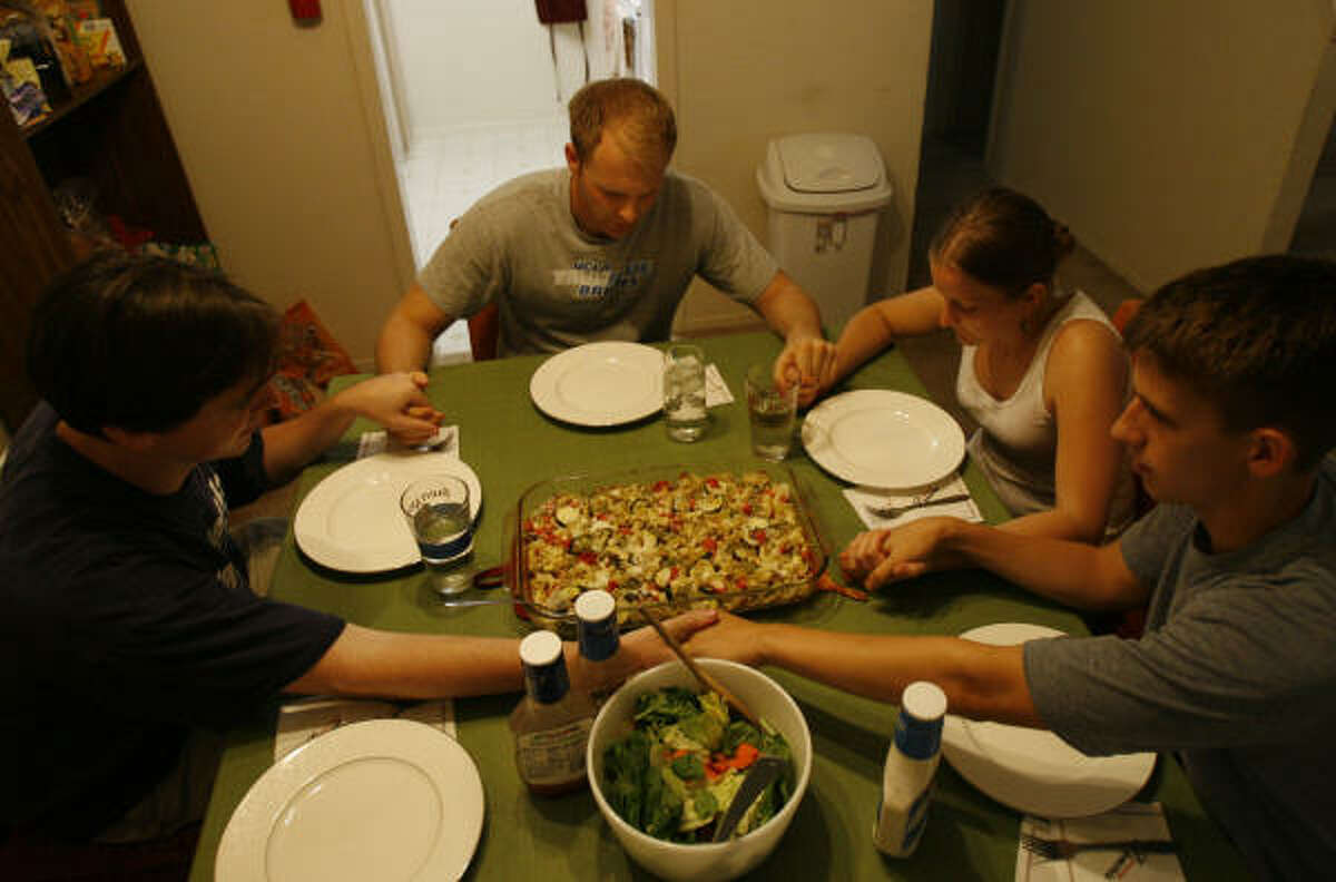 Jesuit Volunteer Corps members Daniel Burke, left, Joe Russell, Jessica Martone, and Tom Byrne, right, pray together before dinner at their apartment. The group abides by the corps' four pillars — spirituality, community, social justice and living simply.