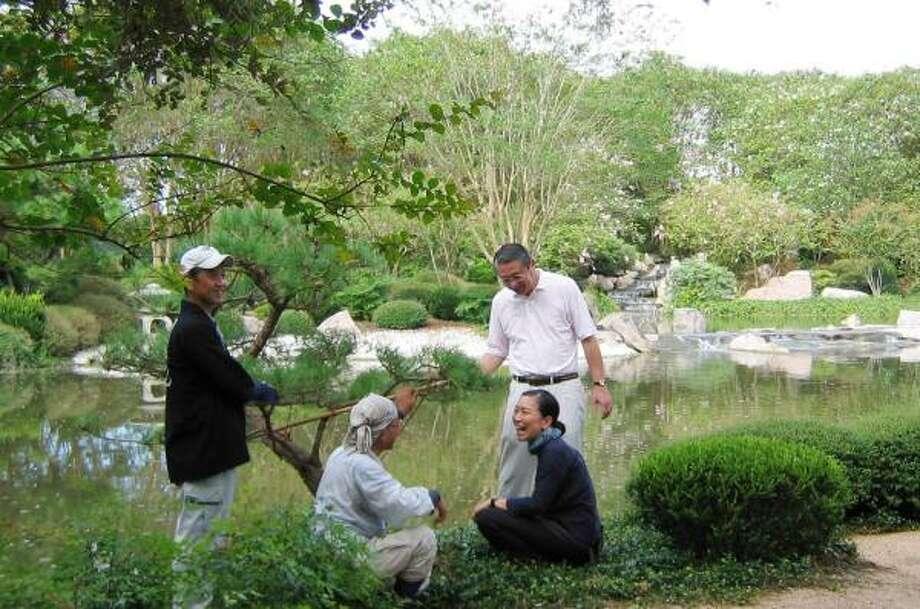 Terunobu Nakai, second from left, studies the Houston Japanese Garden lake with his fellow travelers from Chiba. With him are landscape gardener Hiroshi Iwasaki, left, the city of Chiba's Rikuro Shikama and Aya Hashimoto, Nakai's assistant. Photo: BRENDA BEUST SMITH, For The Chronicle