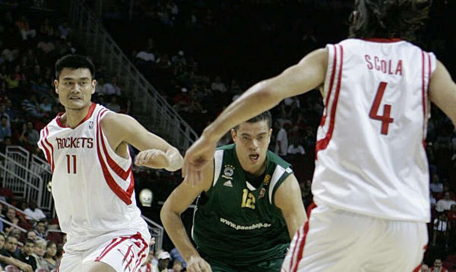 Yao Ming, left, and the Rockets notched their first preseason win, a rout of Kostas Tsartsaris' Panathinaikos. Photo: Pat Sullivan, AP