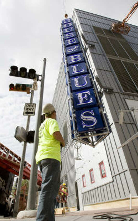 Robert Ivlept helps guide a sign for the House of Blues being installed at the Houston Pavilions. Photo: Brett Coomer, Chronicle