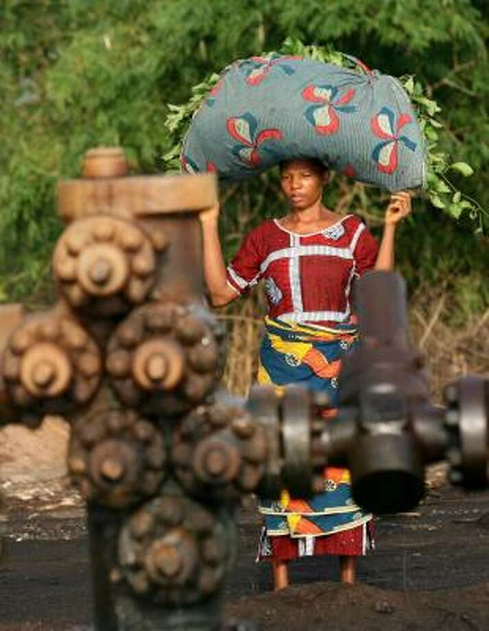 A woman returning from the fields passes a leaking oil well in Kegbara Dere, Nigeria. The country is looking to reform its agreements with international oil companies. Photo: GEORGE OSODI, ASSOCIATED PRESS