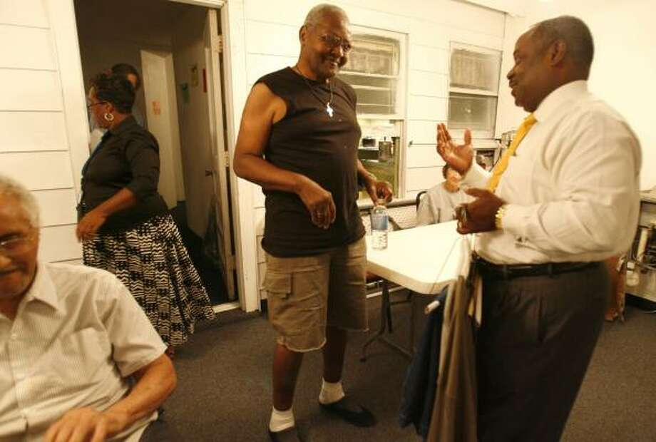 Anvil Gunner, one of 18 elderly evacuees who have been at New Mount Calvary Baptist Church since being displaced by Hurricane Ike, gets some clothes Wednesday from Pastor Ronald Smith. Photo: KAREN WARREN, CHRONICLE