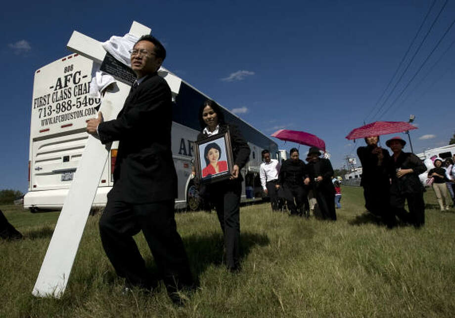 Peter Pham, whose grandmother died in the crash, carries a temporary memorial cross to be erected at the Sherman scene of the accident. Those aboard the bus that crashed were headed to a Catholic festival in Carthage, Mo. Photo: Johnny Hanson, Chronicle