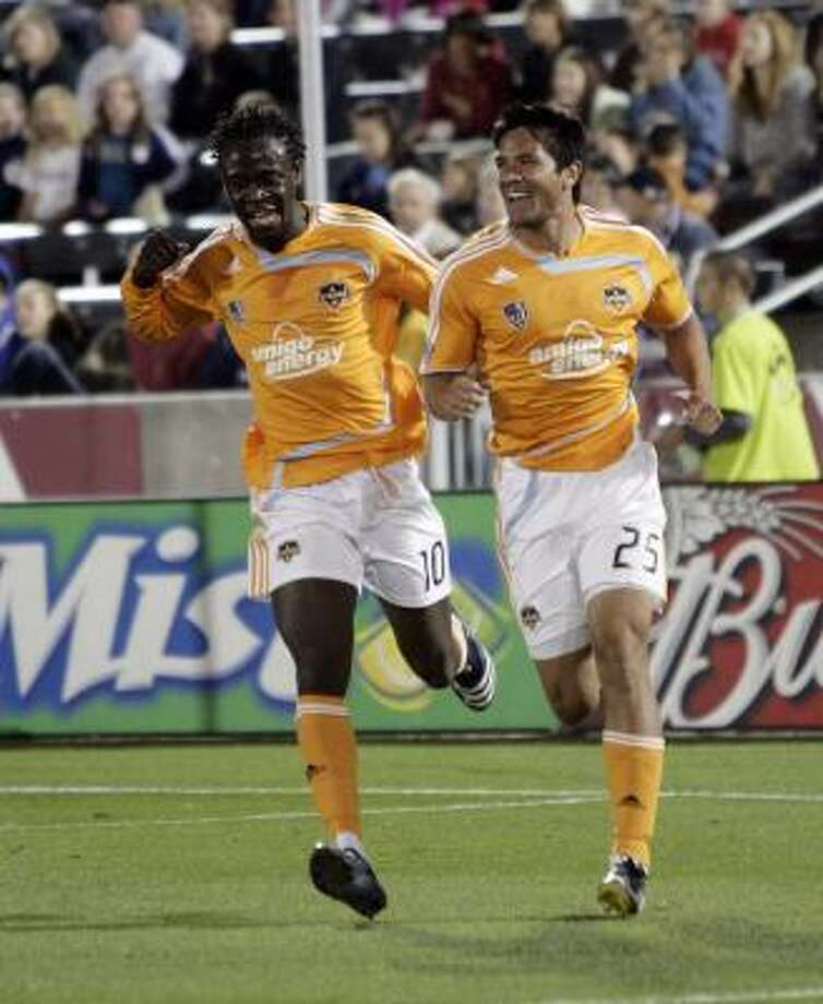 Brian Ching, right, celebrates the first of his two goals with teammate Kei Kamara (10). The Dynamo went on to beat the Colorado Rapids 3-1. Photo: Jack Dempsey, AP