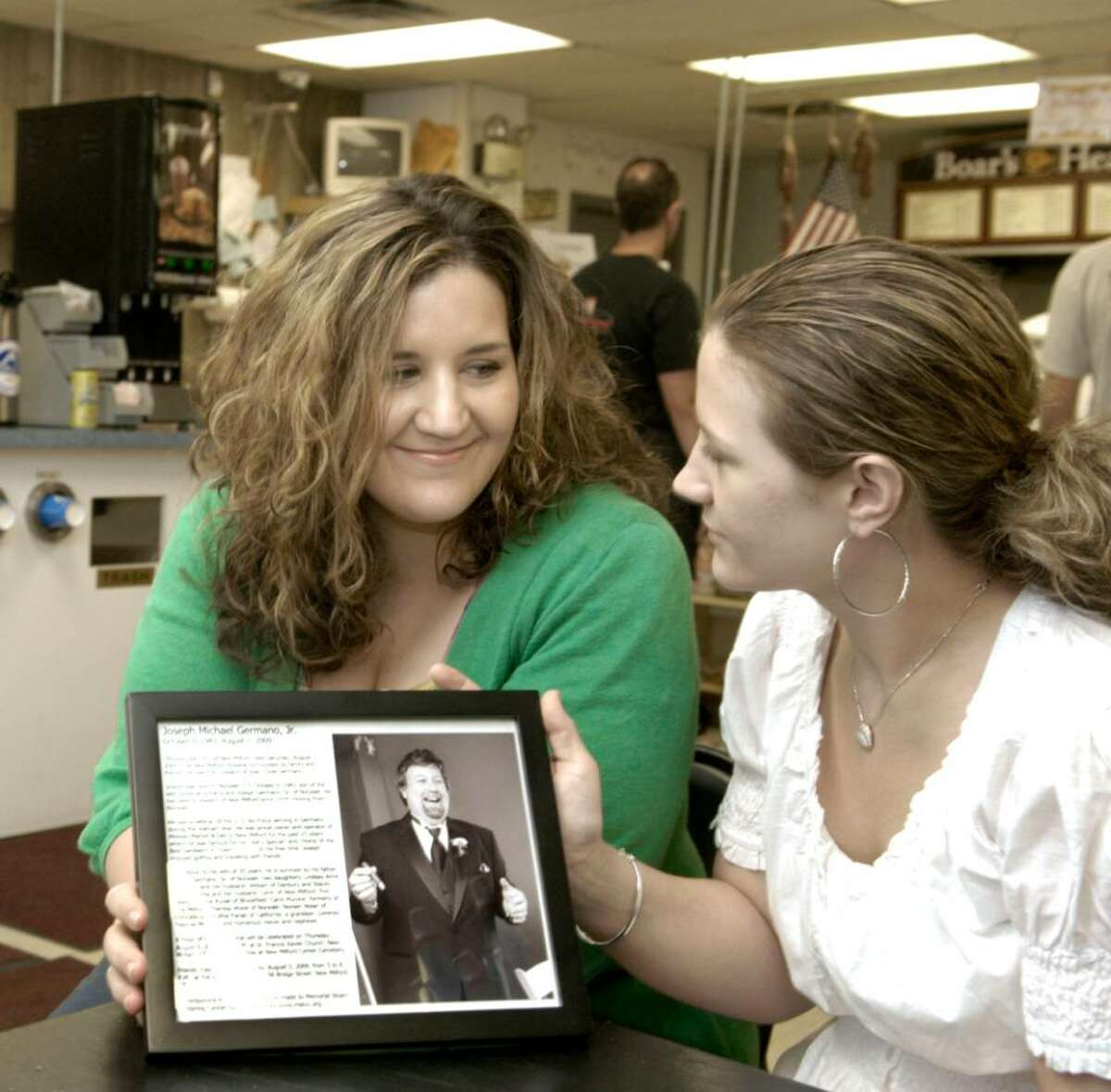 Sisters Lindsay Matthews, 32, of Danbury,left and Stacey Moronta,31 of New Milford, remember their father Joe Germano, long-time owner of the Midway Market in New Milford. Joe died this past weekend after a month-long battle with cancer. Photo taken August 3, 2009 by Carol Kaliff