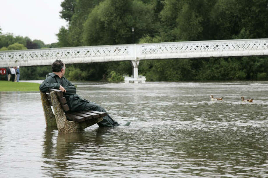 A man sits on a partly submerged bench on the bank of River Thames at Pangbourne, England. Photo: SANG TAN, AP