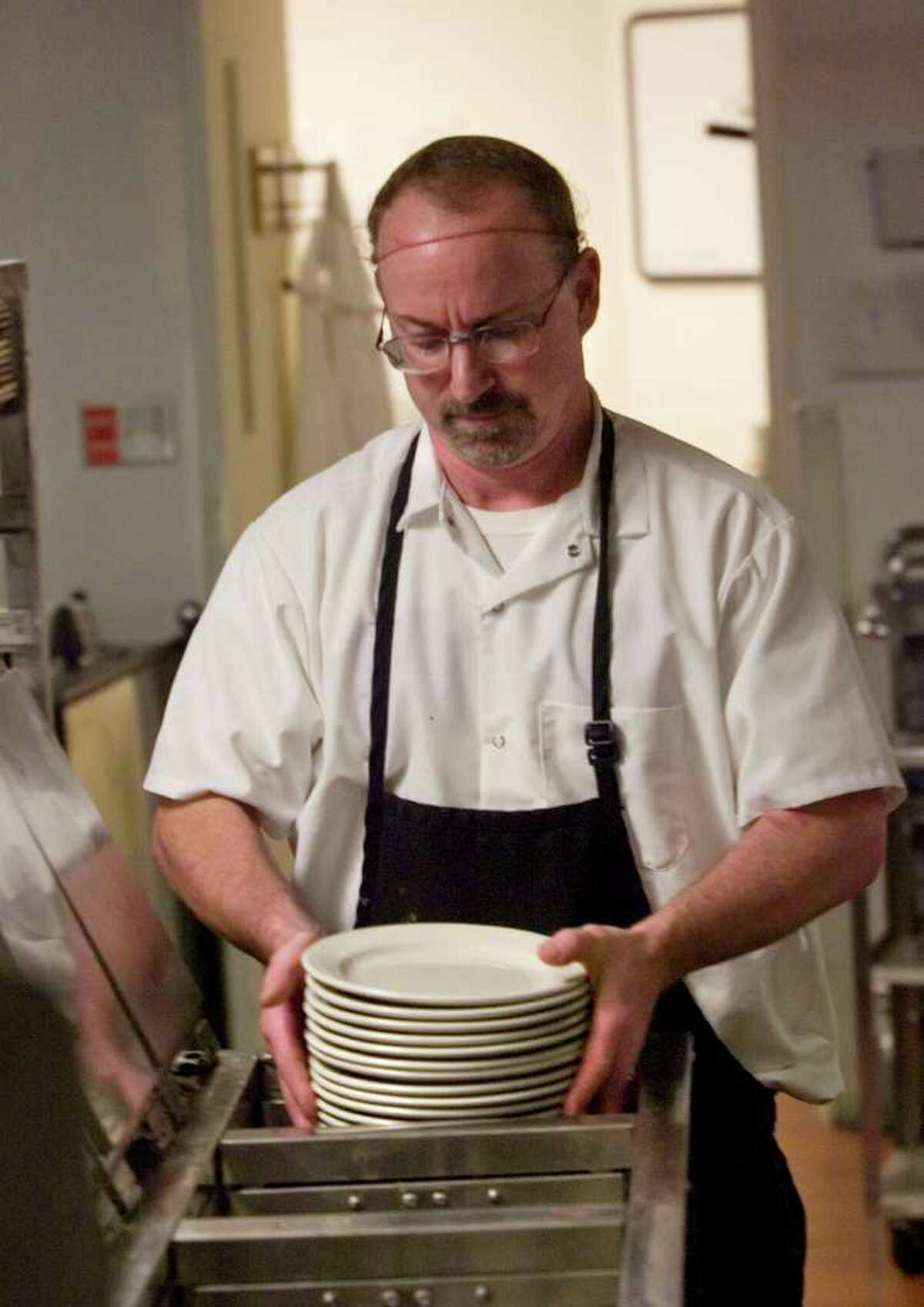 Paul Grewer stacks clean plates at Danbury Hospital on Wednesday, Aug. 10, 2011. The hospital is privatizing all of its food services with an Atlanta-based company, Morrison Management Specialists.