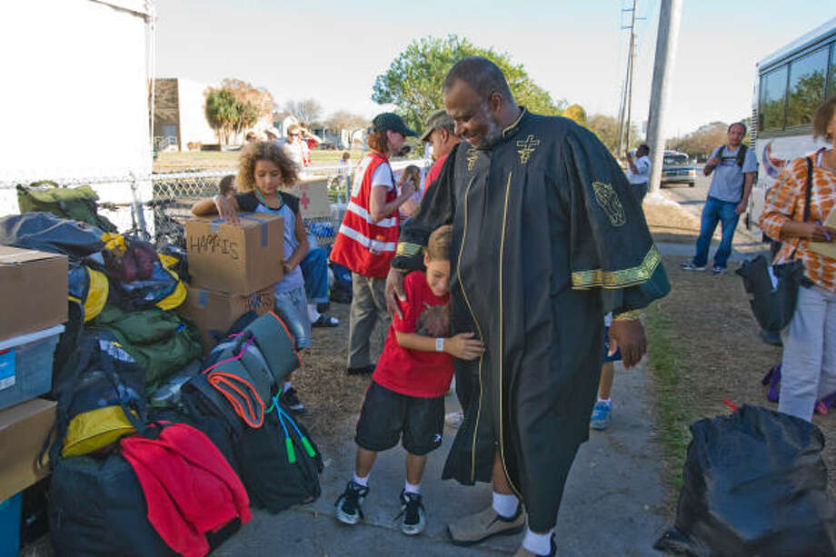 Cameron Harris, 8, left, gets a hug from Minister Darrel Dwayne as he and and other Hurricane Ike evacuees return from San Antonio on Oct. 1 at the Red Cross' Clara Barton Village at the former Alamo Elementary School in Galveston. Photo: Nick De La Torre, HOUSTON CHRONICLE
