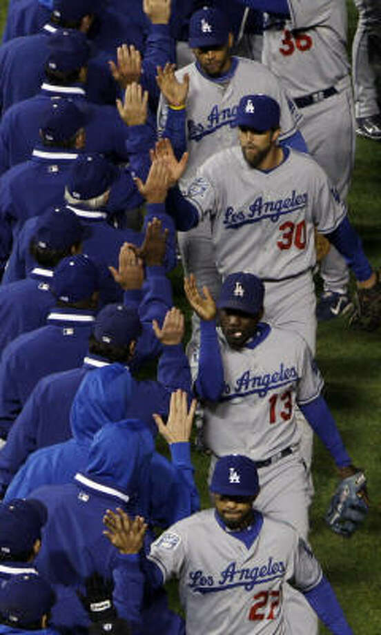 The Los Angeles Dodgers celebrate after the ninth inning. The Dodgers beat the Cubs 7-2. Photo: Tim Donnelly, AP