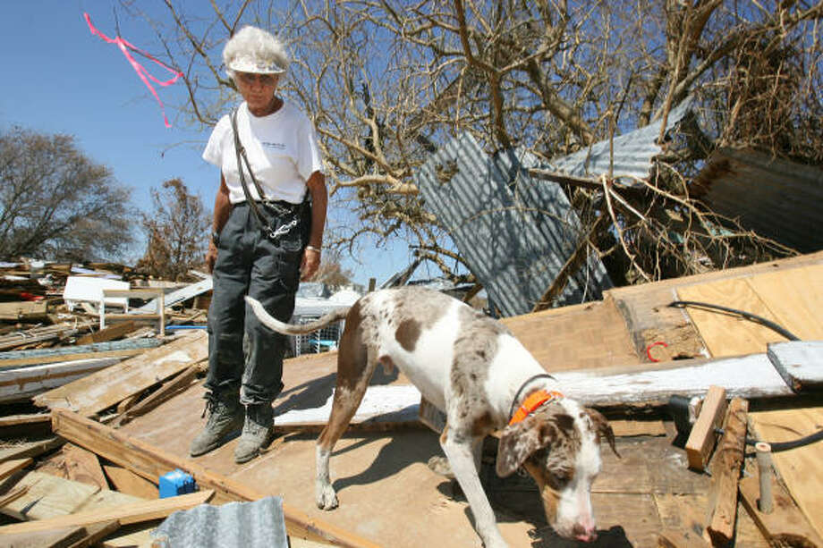 """A pink ribbon dangles from a tree behind JaNa Bickel as she walks away with cadaver dog """"Sonny"""" after he alerted her of human scent underneath debris on Lakewood Drive in Crystal Beach. Photo: Mayra Beltran, Chronicle"""