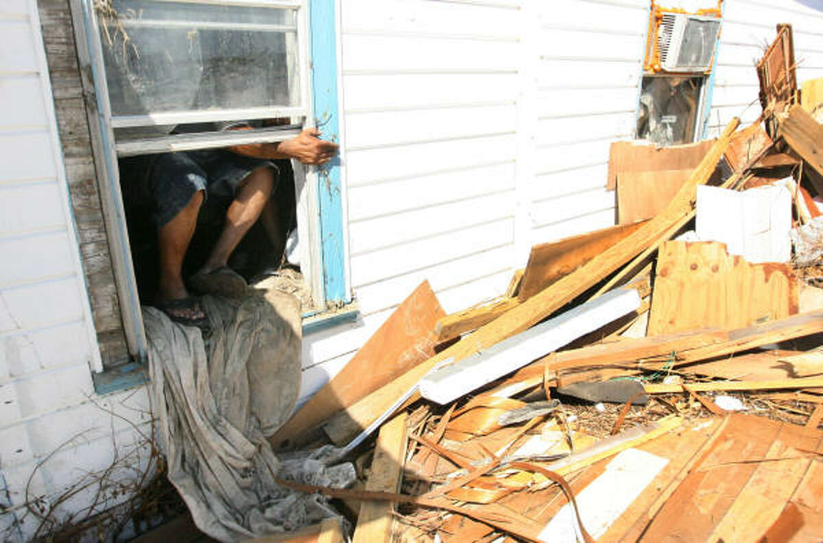 Isaias Lopez climbs out of his house on Crystal Beach Road after his family removed salvageable items from the flooded home. Dogs identified a possible human scent next to his home.
