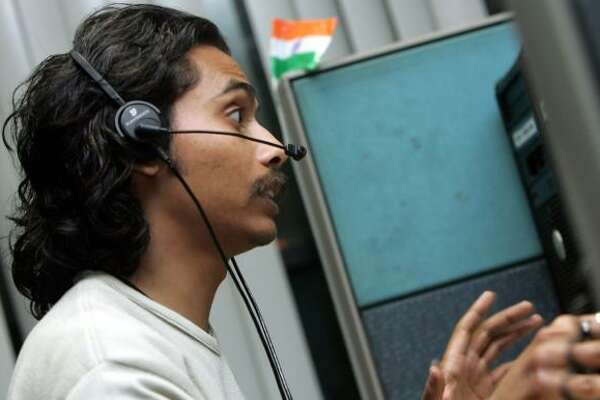 An employee of Convergys Corp., a global leader in call-center outsourcing, speaks with a client in Gurgaon, India.