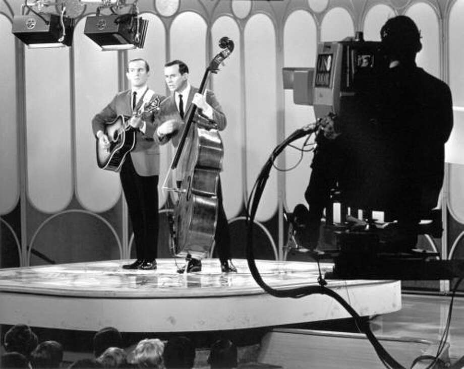 Comedians Tommy, left, and Dick Smothers perform during a taping of The Smothers Brothers Show. Photo: Associated Press