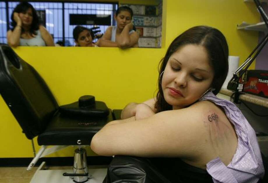 "Yorneglia Boruda strains for a look at her new tattoo of the numbers 666 at a local tattoo parlor. Followers of de Jesús wear the numbers as a sign of their faith in the leader they also call the ""Man Christ Jesus."" Photo: BILLY SMITH II, CHRONICLE"