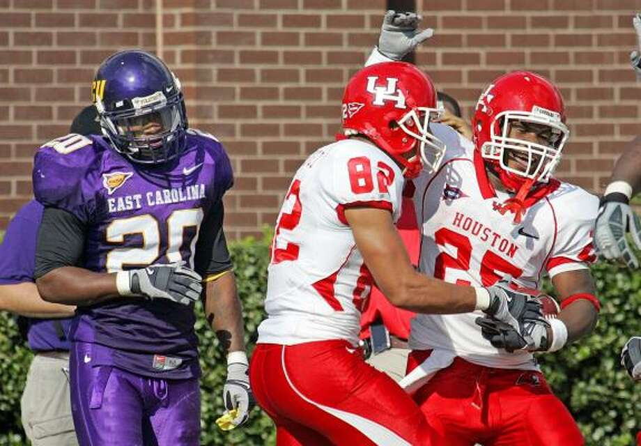 Houston running back Bryce Beall (25) celebrates a touchdown run with teammate Chaz Rodriguez as East Carolina defensive back J.J. Millbrook watches. Houston beat number 23 East Carolina by a score of 41-24. Photo: Karl B DeBlaker, AP