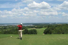 From an elevated tee box with a view of Lake LBJ in the distance, golfers drive the ball about 200 yards over a ravine on Apple Rock's No. 10 at Horseshoe Bay. The par 5 is 567 yards from the back tees.