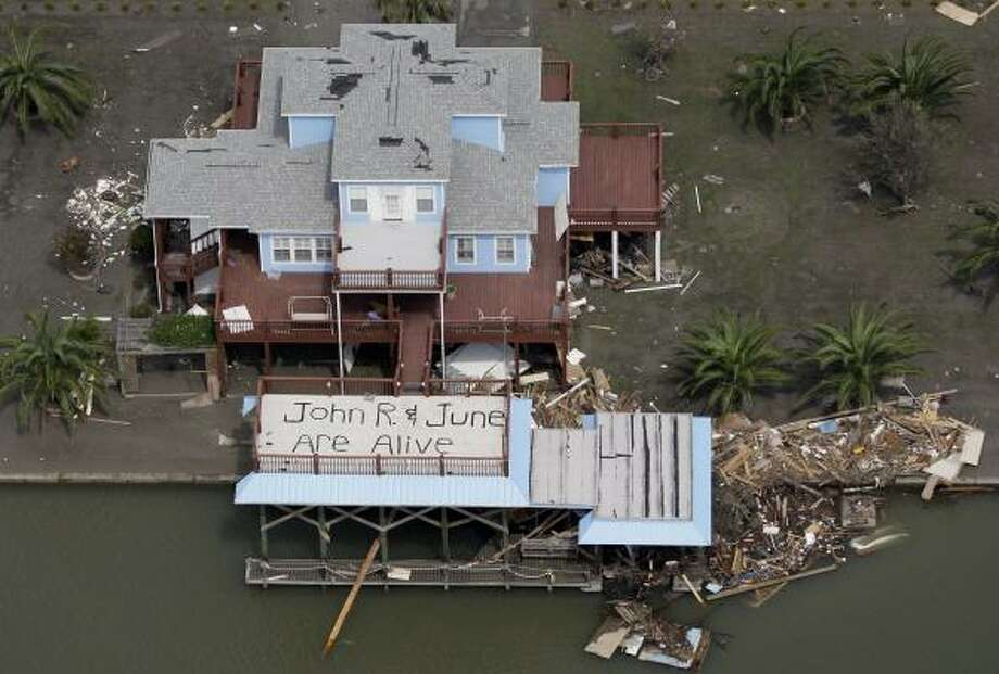 "A sign painted on the deck of a home after Hurricane Ike reads ""John R. & June are alive,"" in Crystal Beach, Texas. Photo: David J. Phillip, AP"