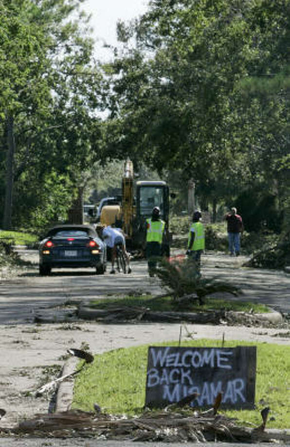 Recovery crews work near a sign welcoming residents back to the Miramar subdivision in Seabrook, Texas. Photo: Frank Franklin II, AP