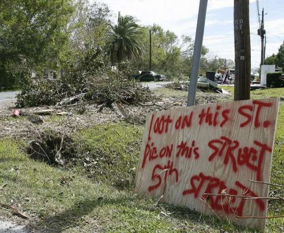 "A sign at the corner of 5th Street and Avenue B reads ""Loot on this St. Die on this Street"" in San Leon in the aftermath of Hurricane Ike. Photo: Kevin M. Cox, AP"