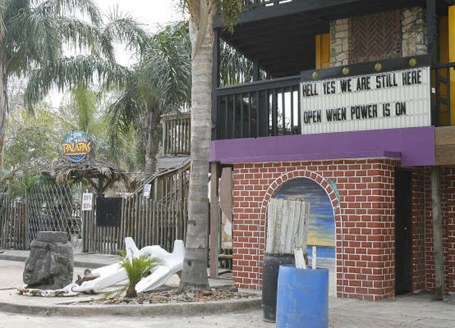 "A sign at Palapa's in Kemah, Texas, reads ""Hell yes we are still here, Open when power is on."" Photo: Kevin M. Cox, AP"