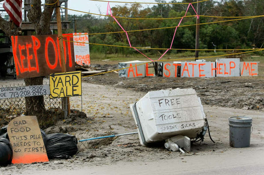 Various signs are seen in front of a home damaged by Hurricane Ike in Seabrook, Texas. Photo: Mark Wilson, Getty Images