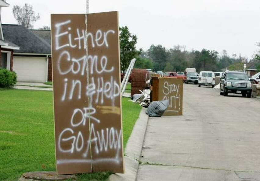 Signs ask the idle to leave a neighborhood in Bridge City, Texas. Surge from Hurricane Ike caused he