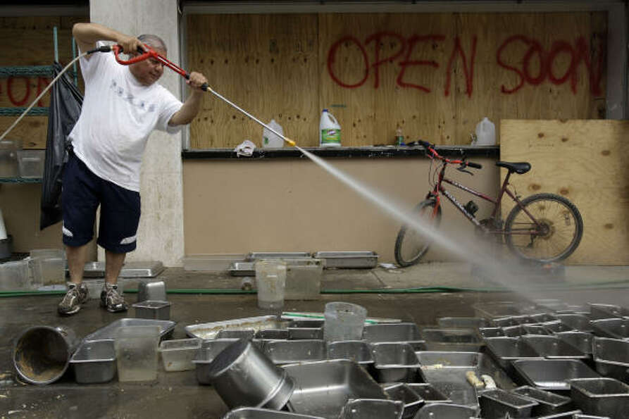 Francisco Paco Vargas, owner of Rudy & Paco restaurant, power washes pans in Galveston.