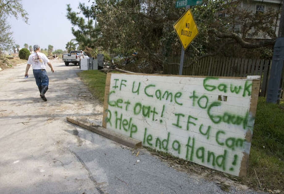 Mark Vermillion walks past a sign he made in front of his home in Seabrook. Photo: James Nielsen, Chronicle