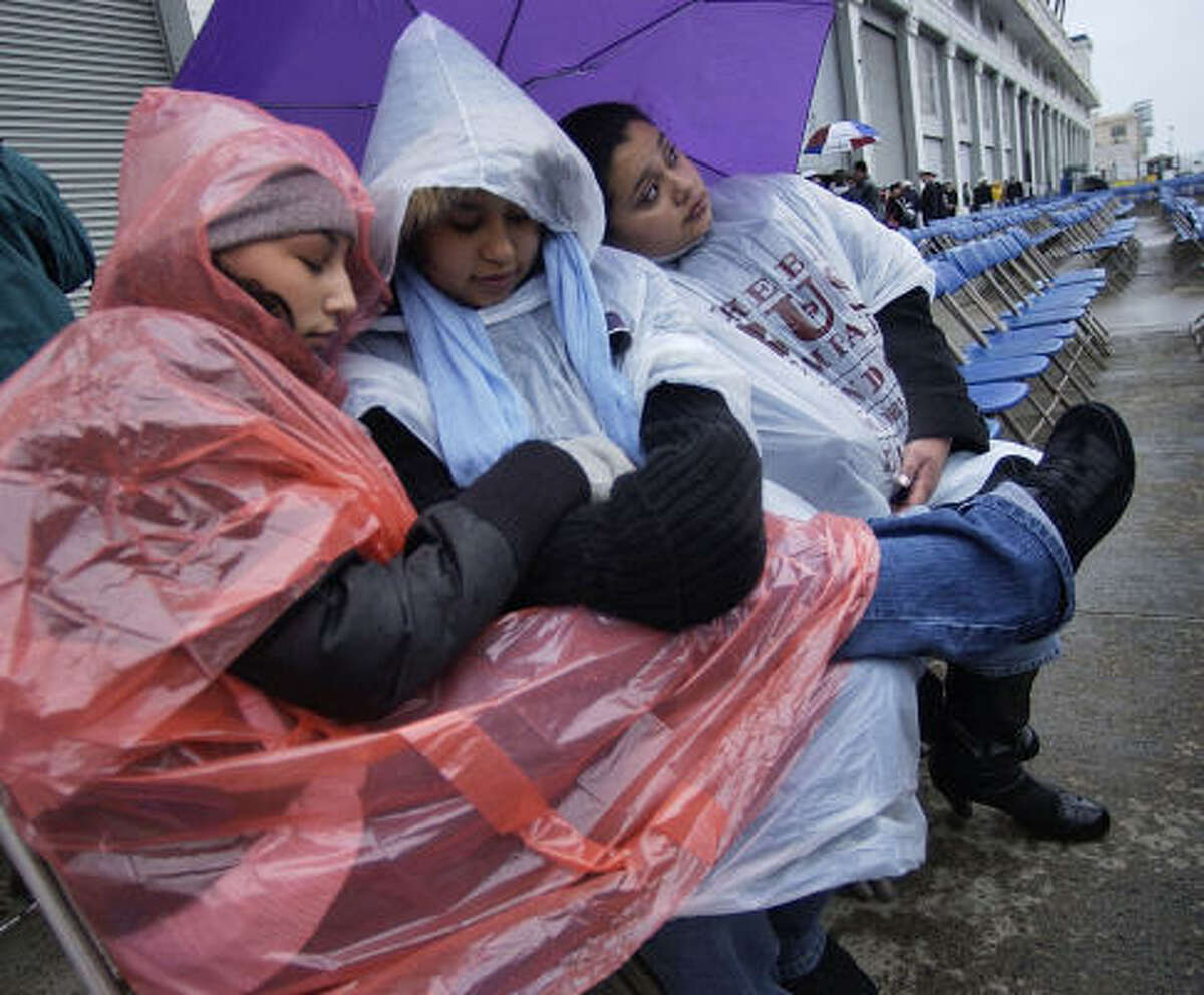 New England faces the remnants of Hurricane Noel. Vanessa Nunez of Turlock, Calif., left, Elizabeth Paz of Newport News, Va., and Jessica Paz of Quantico, Va., wait in the rain for the start of the commissioning ceremony Saturday for the guided-missile destroyer USS Sampson in Boston.